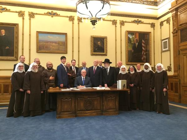 Governor Mike Pence (R-IN) signs his state's Religious Freedom Restoration Act into law, in the presence of   orthodox religious leaders and far-right lobbyists who championed the bill. Photo: twitter.com/govpencein